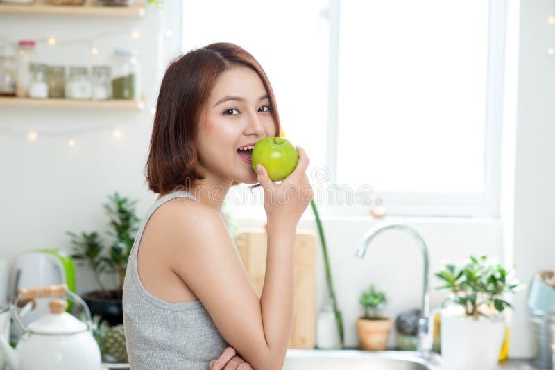 Счастливая молодая азиатская женщина есть зеленое Яблоко на кухне Диета умрите стоковая фотография