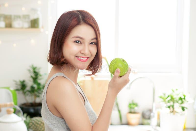 Счастливая молодая азиатская женщина есть зеленое Яблоко на кухне Диета умрите стоковые фотографии rf