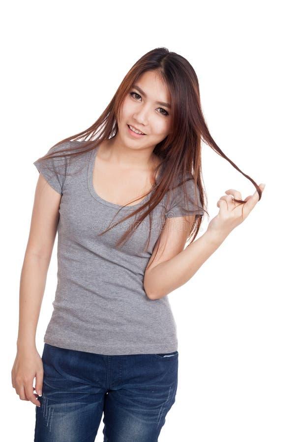 Счастливая молодая азиатская игра женщины с ее волосами стоковое изображение rf