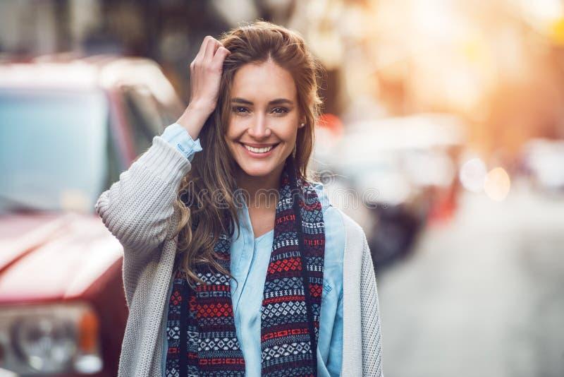 Счастливая молодая взрослая женщина усмехаясь с зубами усмехается outdoors и идущ на улицу города на одеждах зимы времени захода  стоковые фото