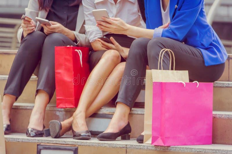Счастливая молодая группа в составе женщины с хозяйственными сумками после ходить по магазинам стоковое фото rf