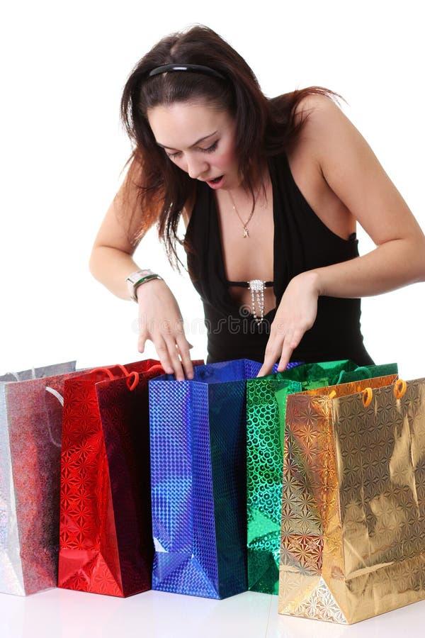 Счастливая молодая девушка брюнет с красочными хозяйственными сумками в сексуальном Д-р стоковое фото