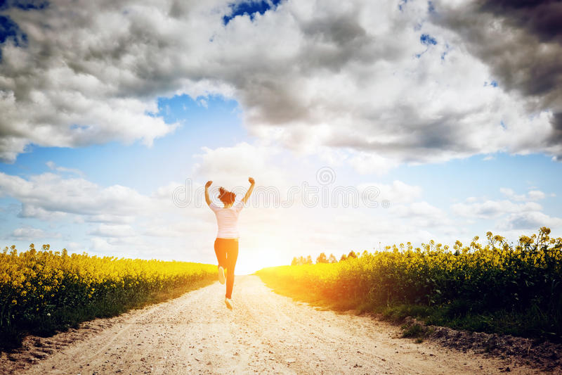 Счастливая молодая женщина бежать и скача для утехи стоковое фото rf