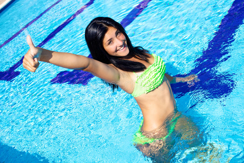 Счастливая молодая женщина в бикини показывая большой палец руки вверх в плавательном бассеине стоковые фотографии rf