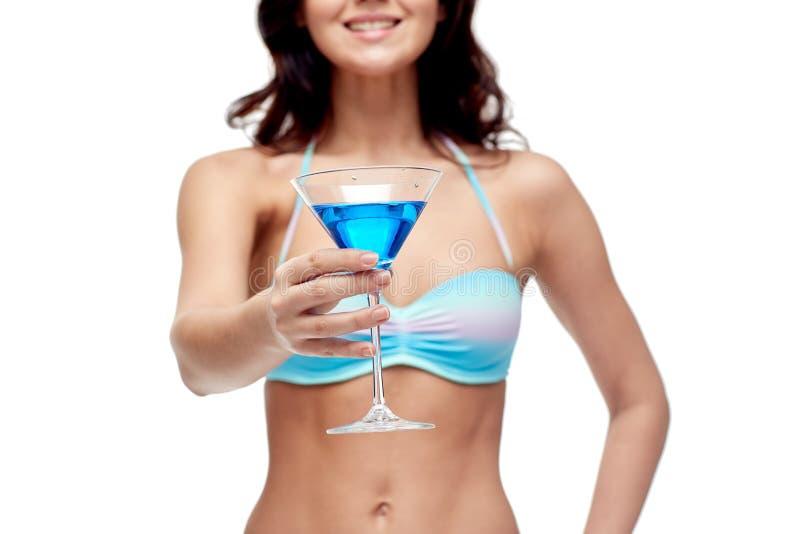 Счастливая молодая женщина в коктеиле swimsuit выпивая стоковые фотографии rf