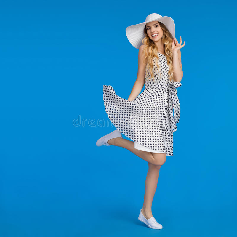Счастливая молодая женщина в платье лета, шляпе Солнця и тапках стоит на одной ноге стоковая фотография rf