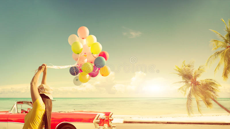 Счастливая молодая женщина держа красочные воздушные шары с плавать стоковая фотография