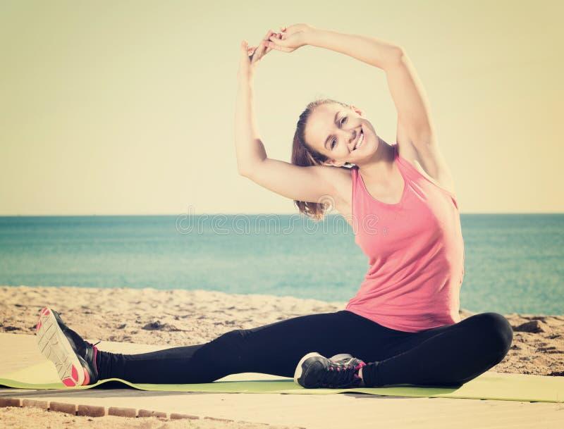 Счастливая молодая женщина делая тренировки гимнастики стоковая фотография rf