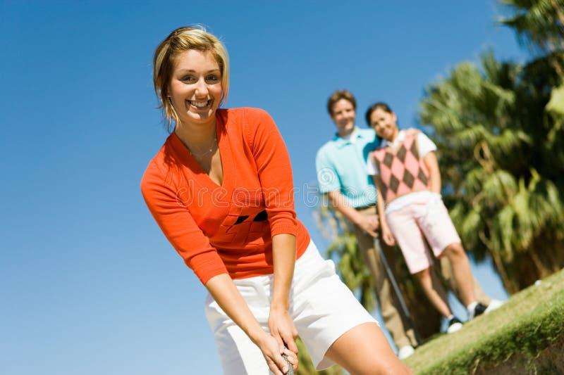 Счастливая молодая женщина играя гольф стоковое изображение