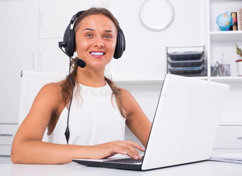 Счастливая молодая женщина используя шлемофон в центре телефонного обслуживания стоковое фото