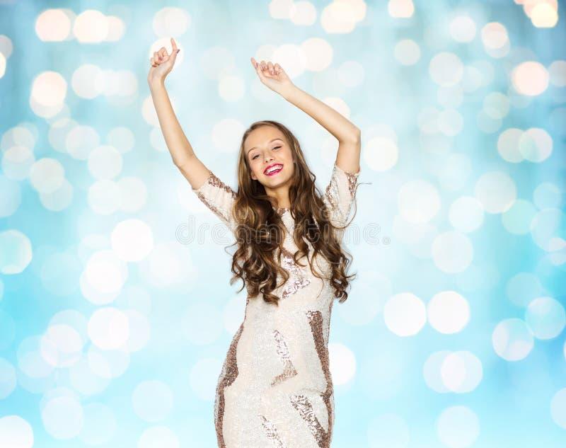 Счастливая молодая женщина или предназначенные для подростков танцы над голубыми светами стоковая фотография
