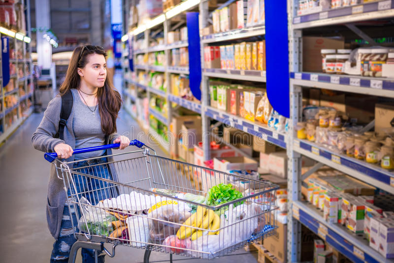 Счастливая молодая женщина нажимая вагонетку в супермаркете стоковые изображения rf