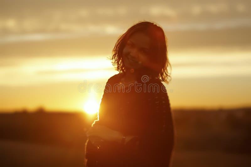 Счастливая молодая женщина на заходе солнца стоковое фото rf