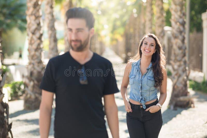 Счастливая молодая женщина на прогулке при парень стоя с руками внутри стоковая фотография rf