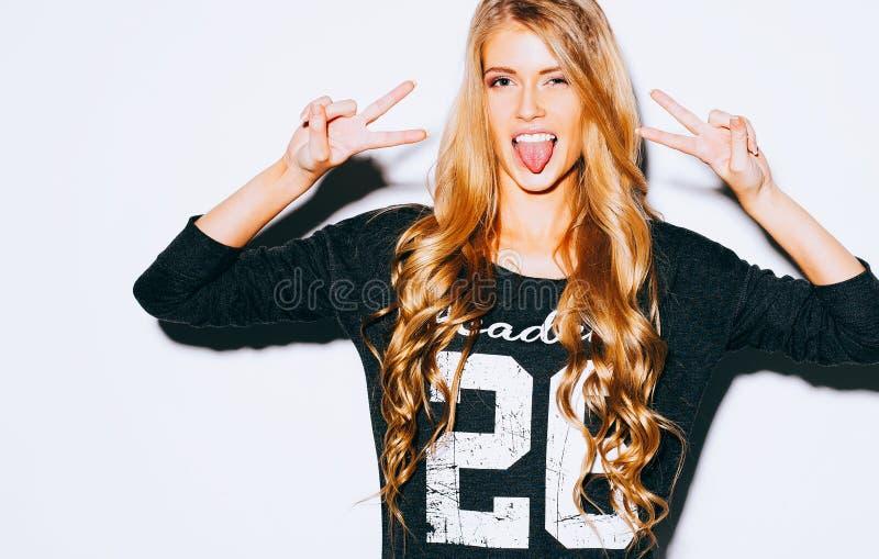 Счастливая молодая женщина показывая знак победы 2 рук и показывая язык на белой предпосылке конец вверх крыто цвет теплый стоковая фотография