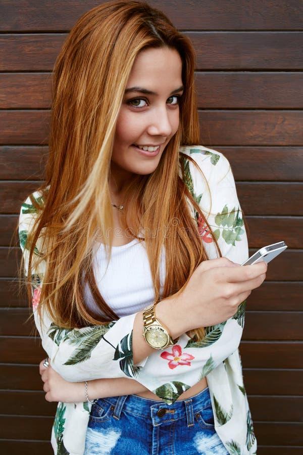 Счастливая молодая женщина посылает текстовое сообщение на ее мобильном телефоне пока стоящ на деревянной предпосылке стены стоковое изображение rf