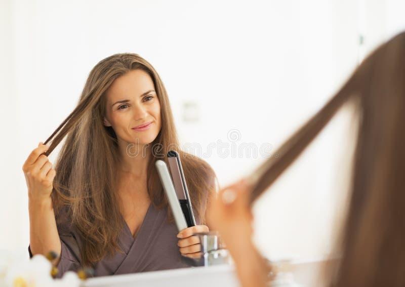 Счастливая молодая женщина проверяя волосы после выправлять стоковая фотография rf