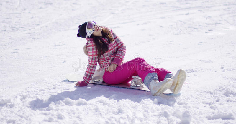 Счастливая молодая женщина сидеть на сноуборде стоковое фото