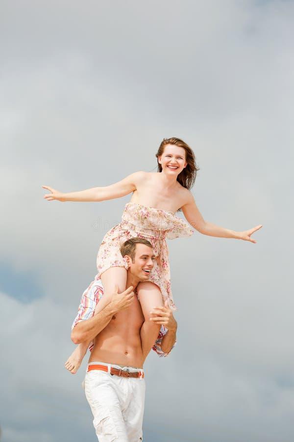 Счастливая молодая женщина сидит на плечах парня по мере того как они играют стоковое изображение