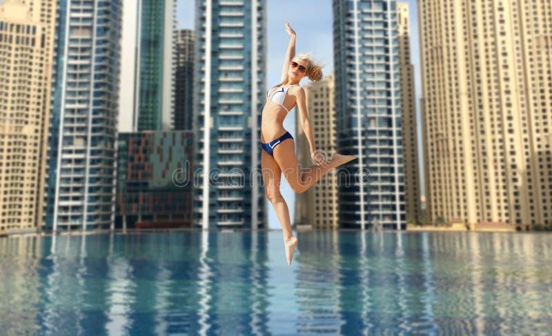 Счастливая молодая женщина скача над бассейном города Дубай стоковые изображения rf