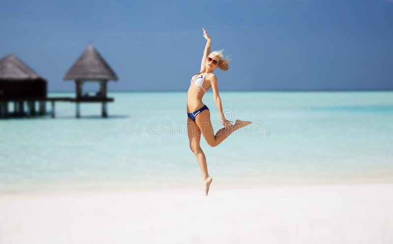 Счастливая молодая женщина скача над экзотическим пляжем стоковое изображение