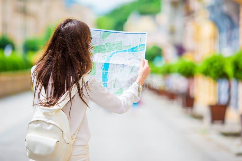 Счастливая молодая женщина с картой города в Европе Путешествуйте туристская женщина с картой в Праге outdoors во время празднико стоковая фотография rf