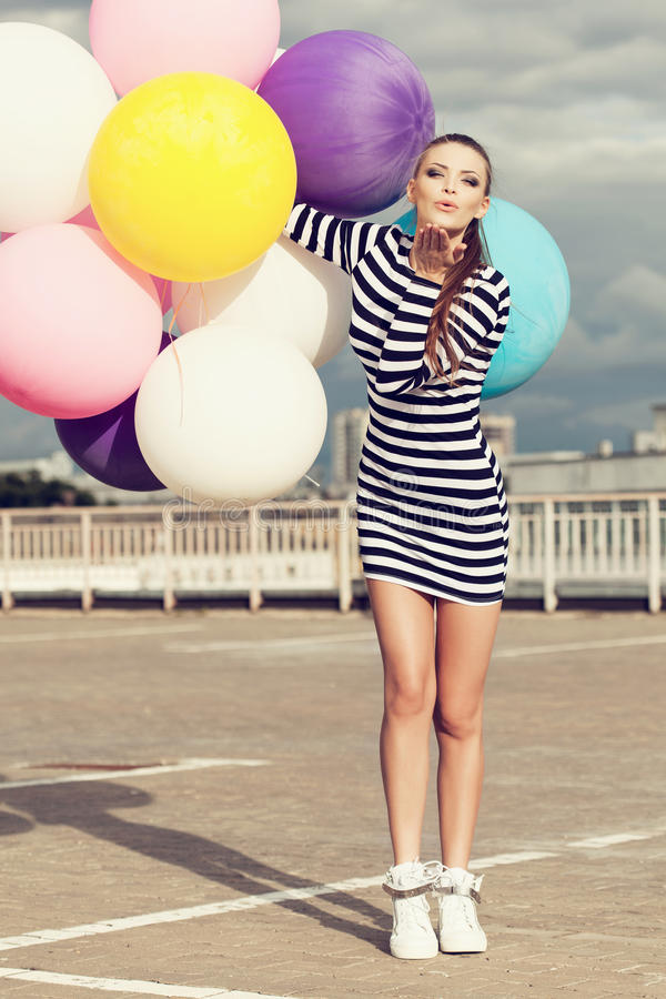 Счастливая молодая женщина с красочными воздушными шарами латекса стоковая фотография rf