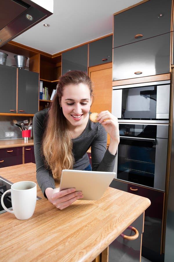 Счастливая молодая женщина читая ее соединенную таблетку, есть в кухне стоковое фото rf