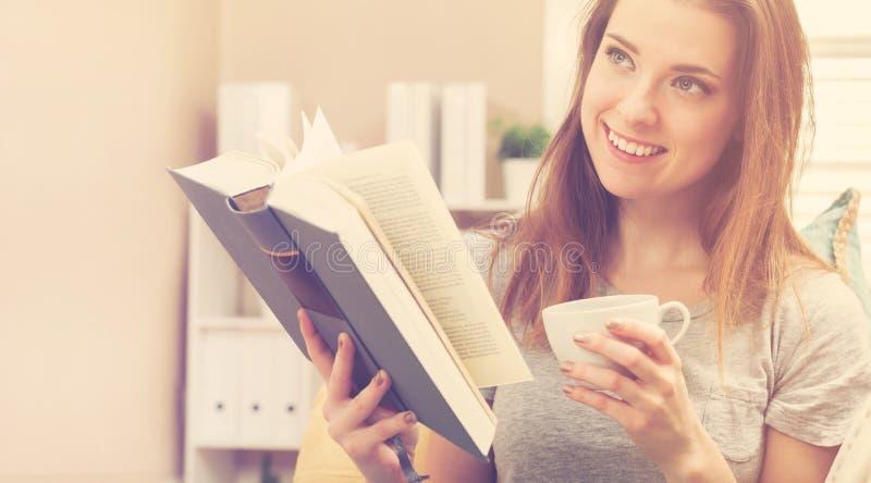 Счастливая молодая женщина читая книгу и выпивая кофе на ее кресле стоковое фото rf