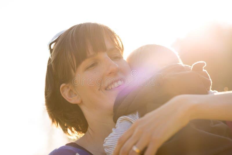 Счастливая молодая защитная мать любяще прижимаясь ее ребёнок стоковые изображения rf