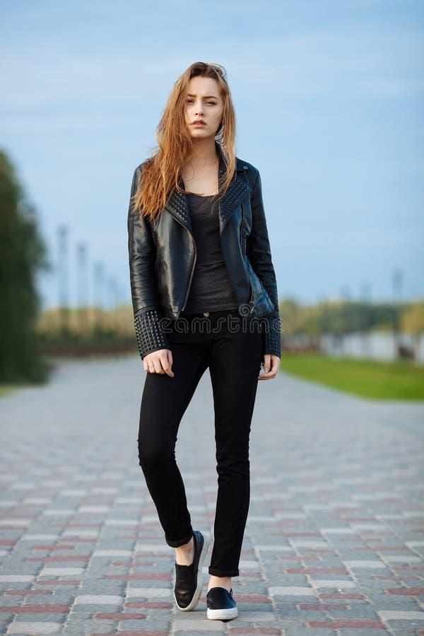 Счастливая молодая красивая женщина в черных джинсах черноты кожаной куртки выскальзывани-на представлять для модельных испытаний стоковые изображения rf