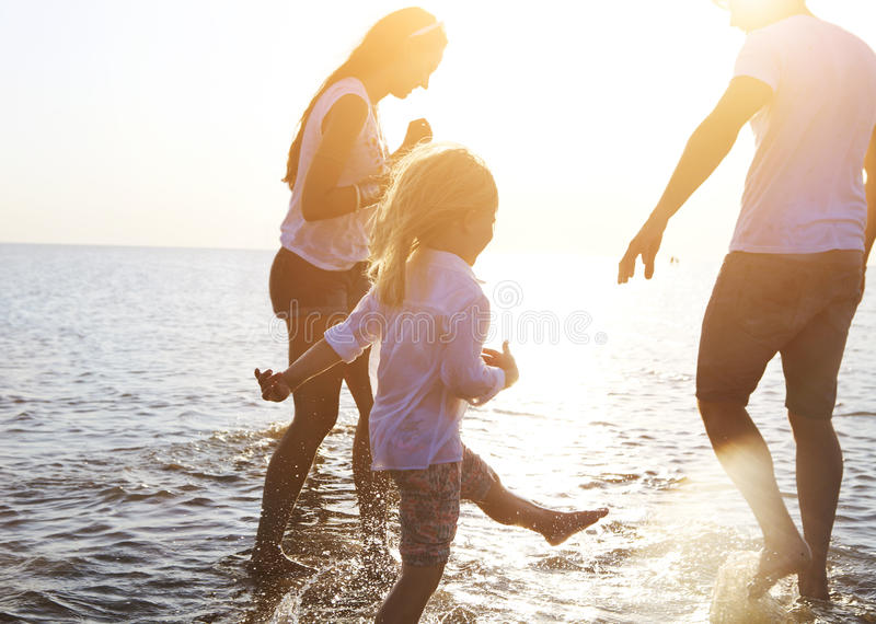 Счастливая молодая семья имея потеху бежать на пляже на заходе солнца стоковые фотографии rf