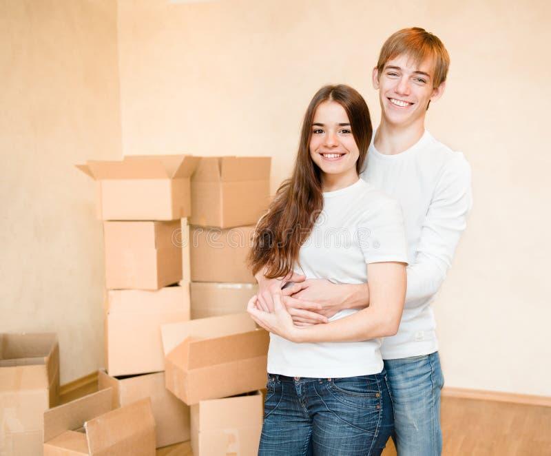 Счастливая молодая семья обнимая на предпосылке картонных коробок стоковые фотографии rf