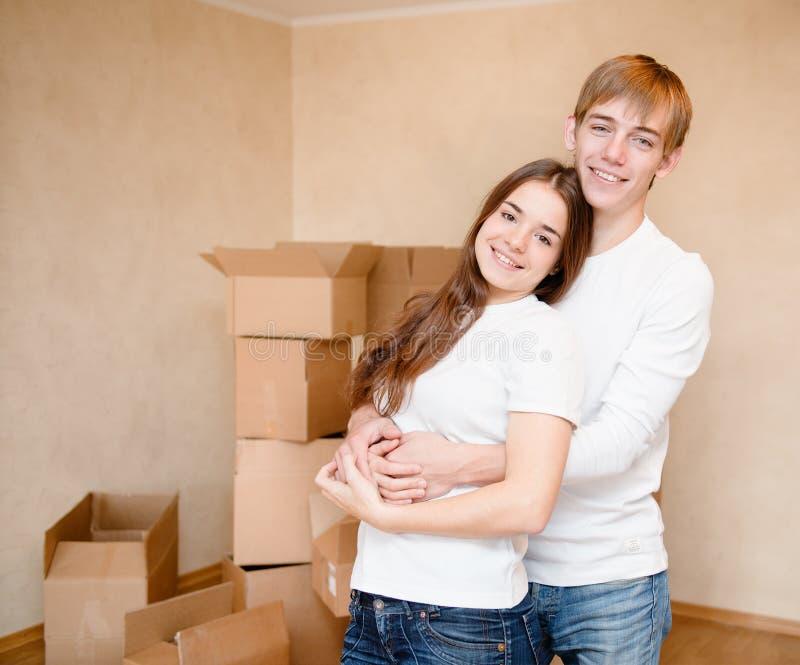 Счастливая молодая семья обнимая на предпосылке картонных коробок стоковое фото rf