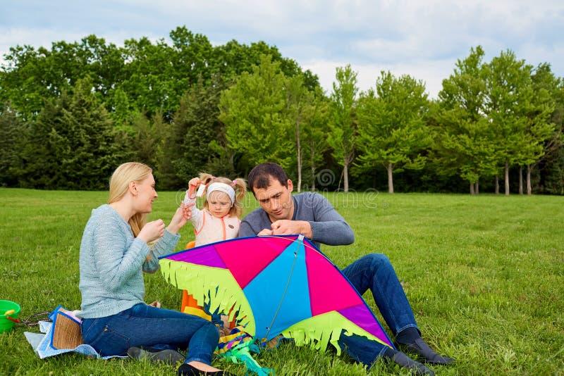 Счастливая молодая семья с летать змей в парке стоковое фото