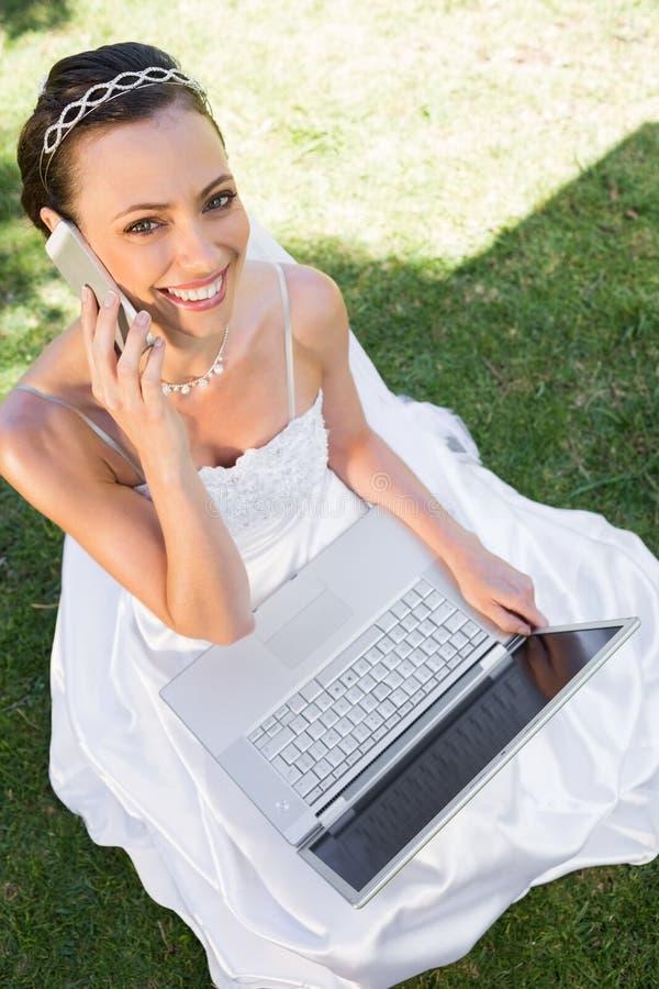 Счастливая невеста с компьтер-книжкой используя мобильный телефон на траве стоковая фотография