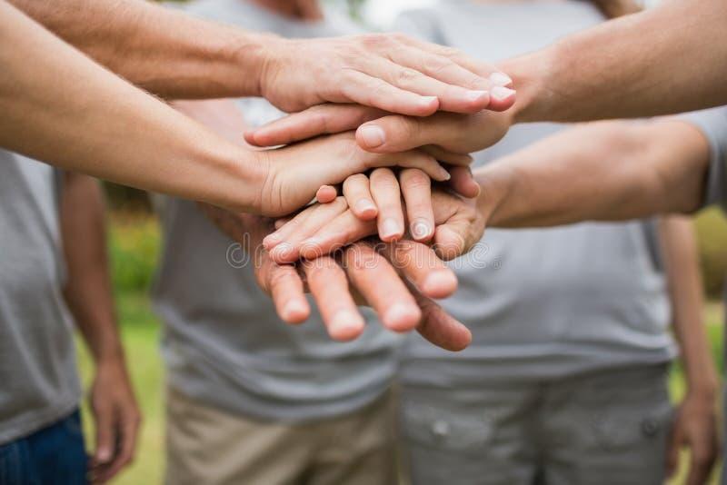 Счастливая добровольная семья кладя их руки совместно стоковая фотография rf