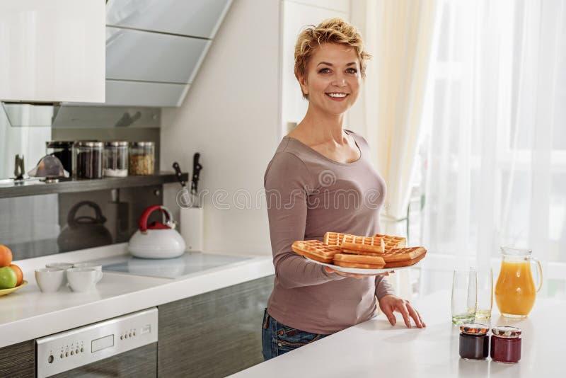 Счастливая домохозяйка варя завтрак в кухне стоковое изображение