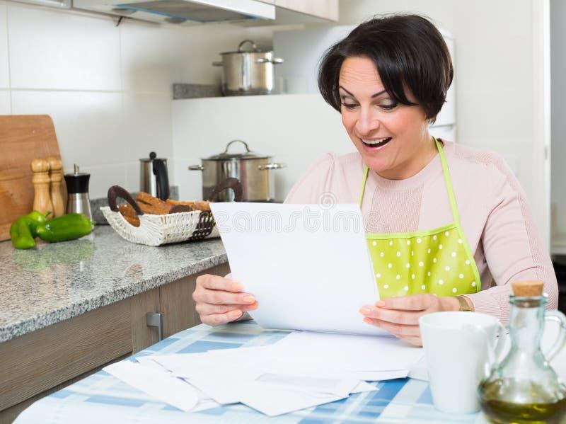 Счастливая домохозяйка с первоклассными векселями в кухне стоковое изображение