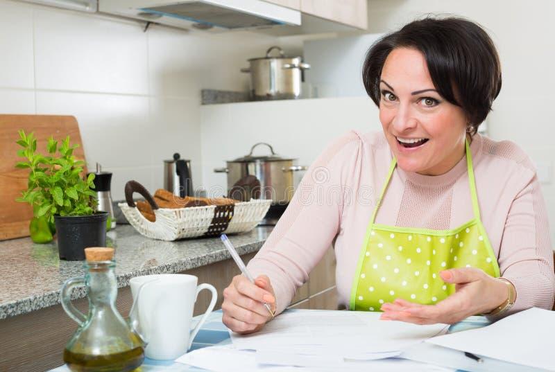 Счастливая домохозяйка с первоклассными векселями в кухне стоковые фото
