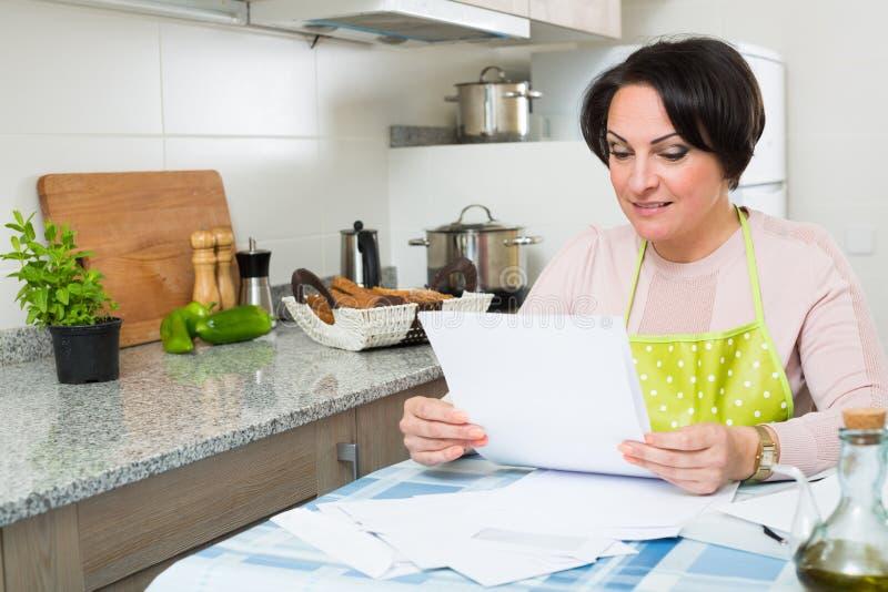 Счастливая домохозяйка с первоклассными векселями в кухне стоковое изображение rf