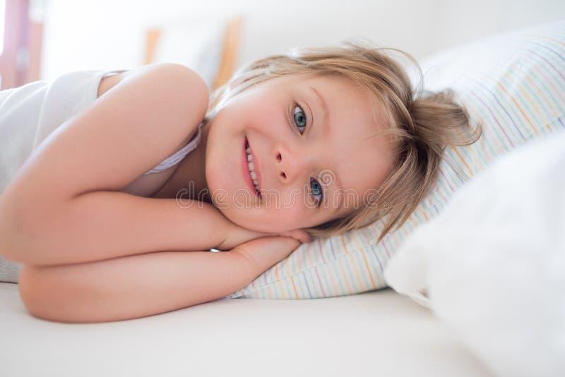 Счастливая дочь девушки просыпая вверх усмехаться смотрящ камеру на родительской кровати ` s на утре Счастливая расслабленная сем стоковое изображение rf