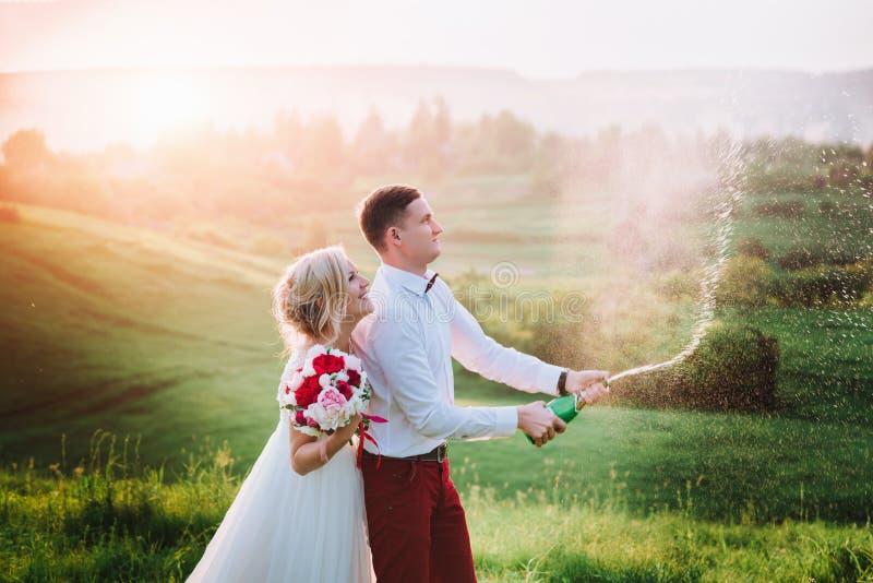 Счастливая пара свадьбы с buttle champaine и брызгает шампанского стоковое изображение