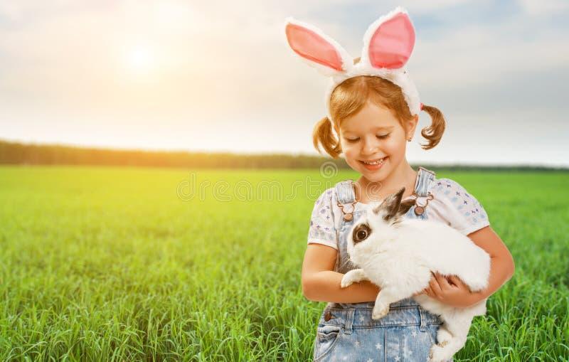 Счастливая пасха! Милая девушка ребенка с кроликом в природе стоковая фотография
