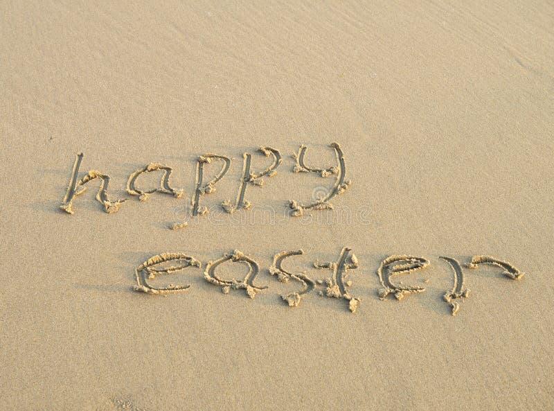 Счастливая пасха написанная на песке стоковая фотография