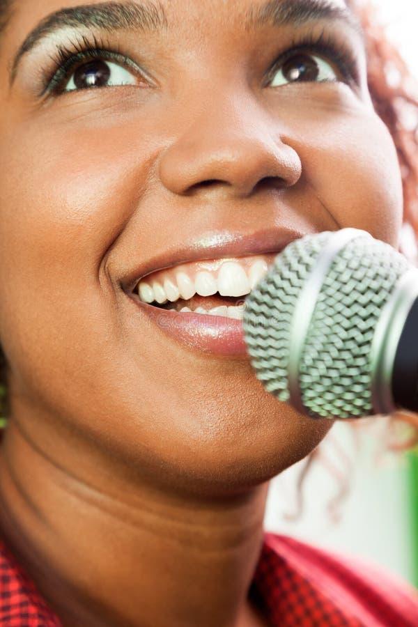 Счастливая певица смотря вверх пока выполняющ стоковые фото