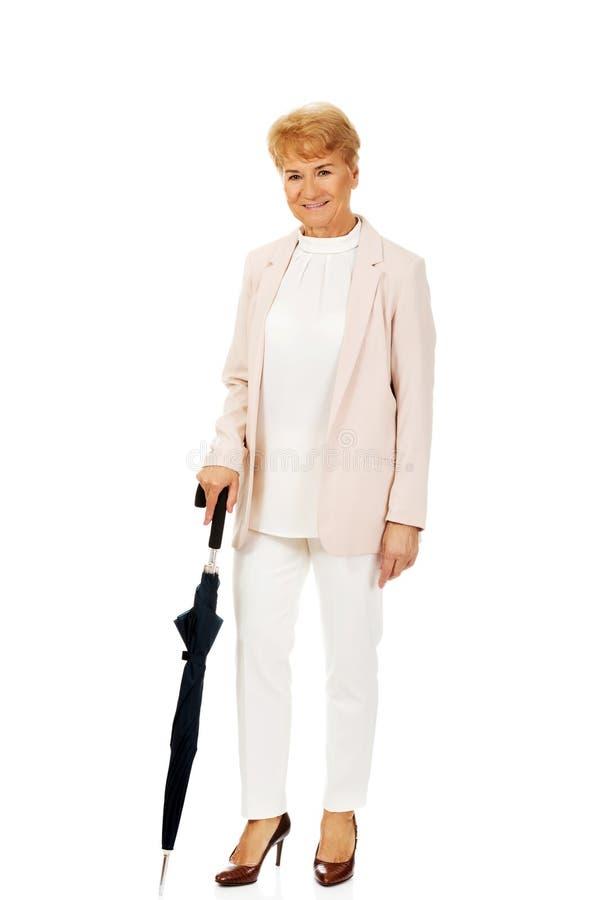 Счастливая пожилая бизнес-леди держа зонтик стоковое фото