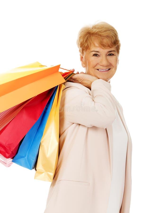 Счастливая пожилая бизнес-леди держа хозяйственные сумки стоковое изображение