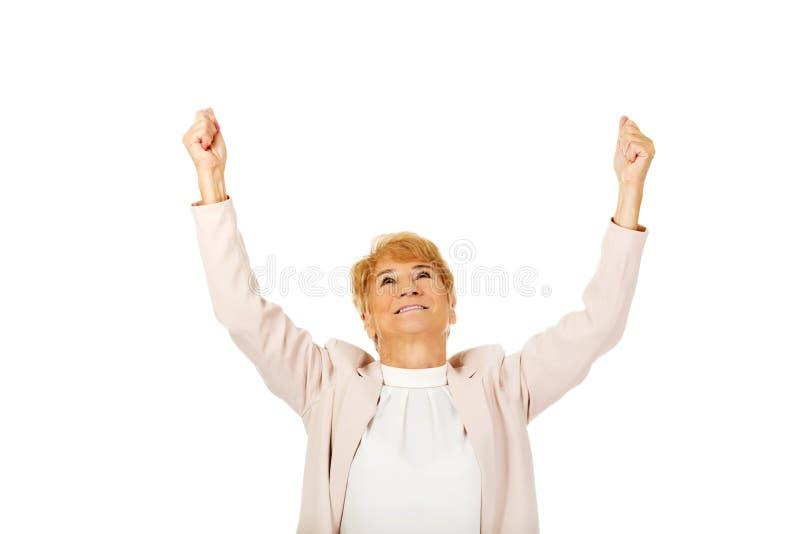 Счастливая пожилая бизнес-леди с оружиями вверх стоковые фото