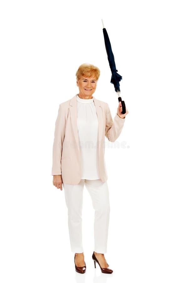 Счастливая пожилая бизнес-леди указывая вверх с зонтиком стоковое изображение
